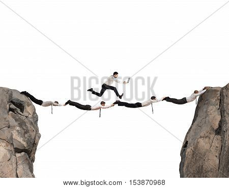 Businessmen working together to form a bridge between two mountains
