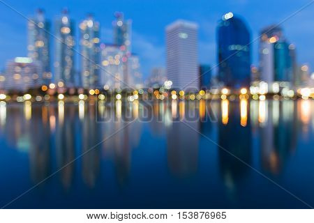 Twilight blurred bokeh lights city downtown with reflection, abstract background
