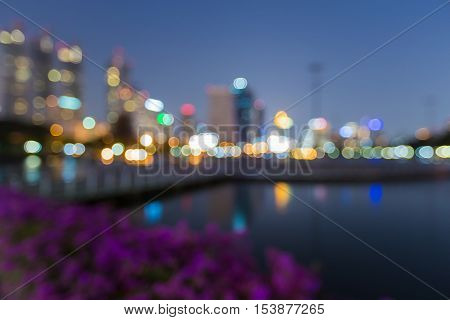 Blurred bokeh lights office building background with reflection in public park
