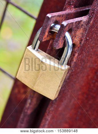 Old, rusty padlock locked on an entrance. Close-up shot.