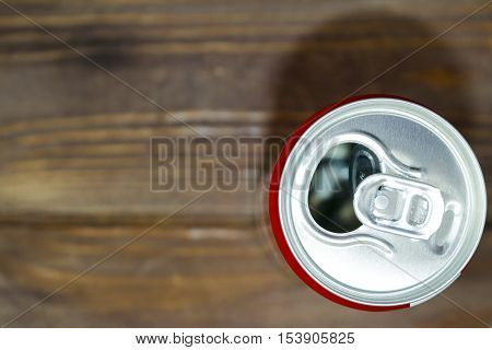 Empty blank soda or beer trash ten on the old wooden background. Red Bank.