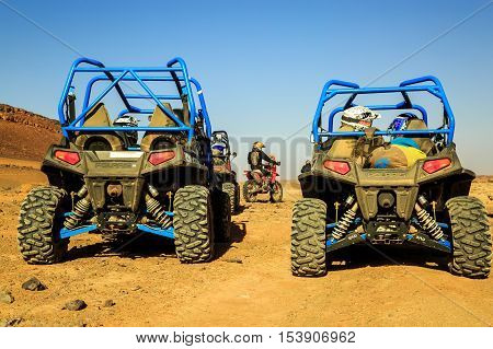 Merzouga Morocco - Feb 24 2016: back view on blue Polaris RZR 800 group of pilots with a bicker in Morocco desert near Merzouga. Merzouga is famous for its dunes the highest in Morocco.