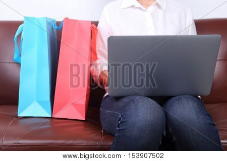 Woman sit on sofa with shooping bag beside and using laptop