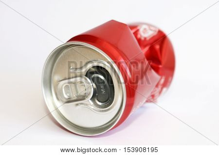 Crumpled empty blank soda or beer for garbage, on a white background.Crumpled aluminum can.Jar red.