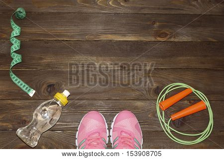 Sport shoes, skipping rope and water bottle on wooden background. Sport, diet and healthy lifestyle concept. Clothing and sports accessories for fitness. The view from the top. The place to advertise.