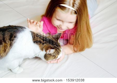 Adorable little girl feeding her cat at home