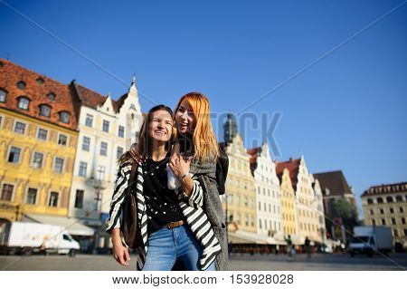 Two nice girls stand in the middle of the paved area having embraced. Girlfriends happily smile. They rejoice to a meeting. Warm sunny day. Bright blue sky. On a background beautiful ancient houses.