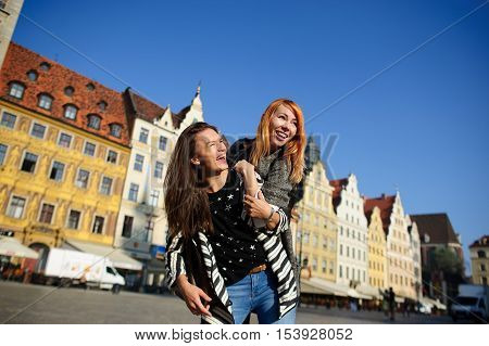 Two young women stand having embraced. On faces of girlfriends happy smiles. They rejoice to a meeting. Warm sunny day. On a background beautiful ancient buildings of the European city.