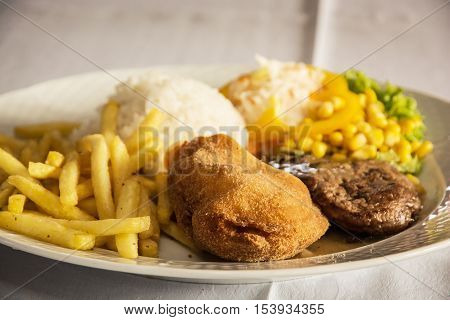 Festive menu of tasty chicken breast stuffed with ham and cheese with rice fries and pork with sauce and mushrooms. International cuisine. Food theme. Large portion.