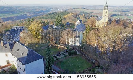 View of the Erzgebirge in Saxony, Germany; meadows, fields, forests,  villages and in the foreground the town church and some houses of the small town of Augustusburg; landscape in the late autumn from the bird's perspective