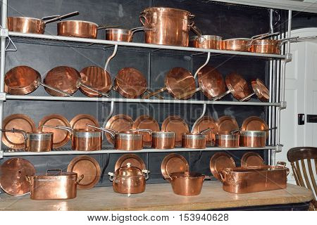 Four shelves of Antique copper cookware in rows