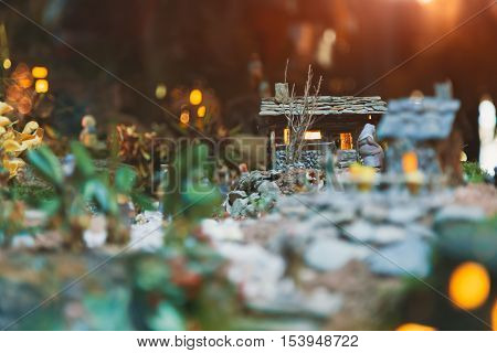 Posed handstitched toy Christmas nativity scene. Small houses and figures