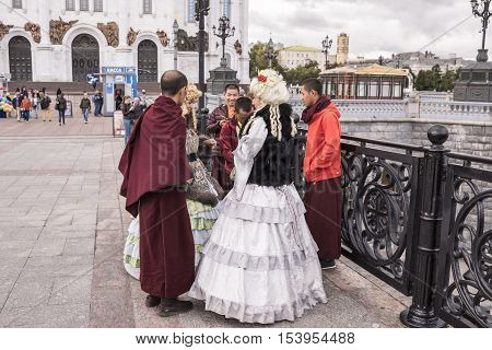 Moscow Russia -September 09 2016: Roma women in ancient dresses make a fool of Tibetan monks at the Patriarchal bridg