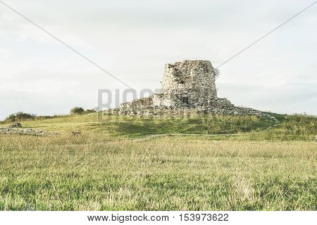 Ruins of ancient city in prehistorical time located in Sardinia island - Nuraghe culture is a 1500 a.c civilization - Concept of visiting italian's old stronghold and ruins - Vintage retro filter