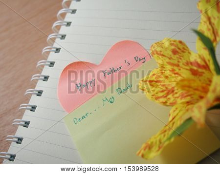 Short note happy father 's day my daddy created on notebook with created flower