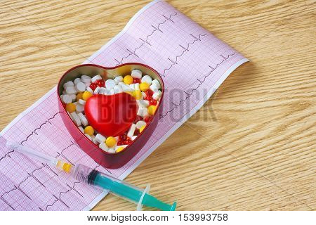 syringe cardiogram box of tablet and red heart on wooden table