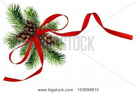 Christmas arrangement with pine twigs cones and red silk ribbon bow isolated on white
