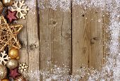 Gold Christmas Ornament Side Border With Snow Frame On A Rustic Wood Background poster
