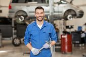 car service, repair, maintenance and people concept - auto mechanic man or smith with wrench at work poster