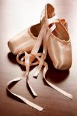 stock photo of ballet shoes  - Pink satin ballet shoes on dark floor in slight soft focus - JPG