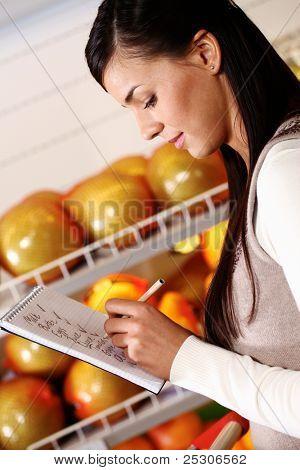 Bild hübsche Frau tickt, was sie im Supermarkt gekauft hat