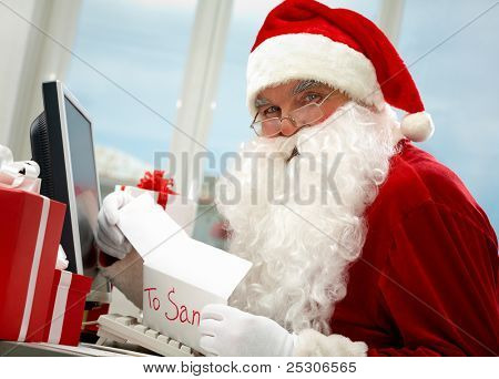 Santa Claus holding Christmas letter and looking at camera