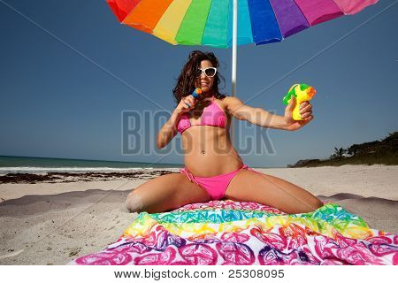Young Brunette Woman At The Beach Surfing With Squirt Guns