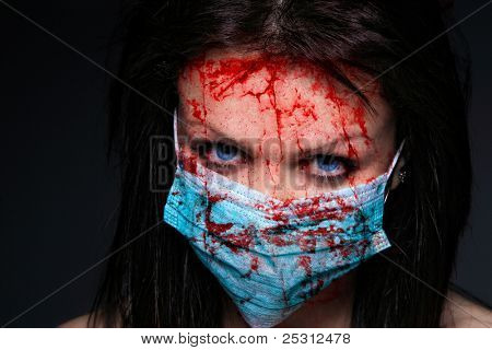 Young nurse in mask covered of blood