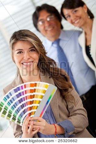 Business couple with an interior designer choosing a color to paint the office