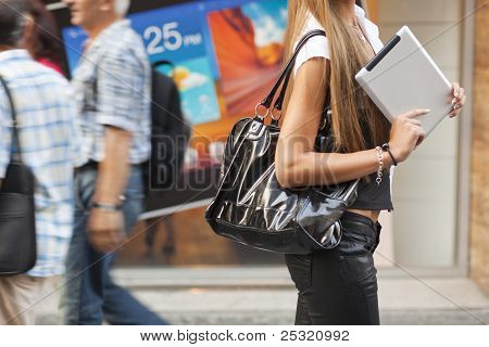 Young Woman With Tablet Computer Walking On Street