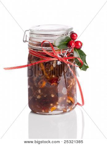 Jar of Christmas mincemeat tied with a festive ribbon with holly and berries on a white background