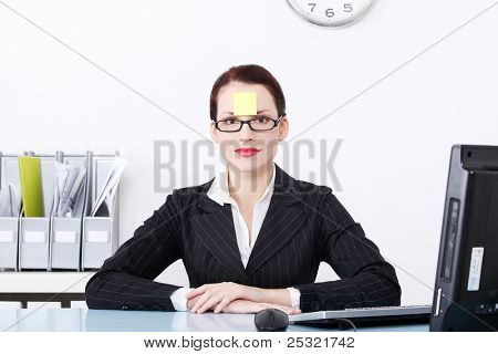Pretty caucasian businesswoman sitting in the office with post it note on her forehead.