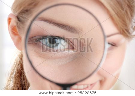 The woman with a magnifier in a hand on the isolated background