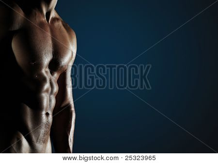 Part of a wet man's body on a dark blue background with copyspace