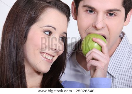 young man eating apple and girlfriend