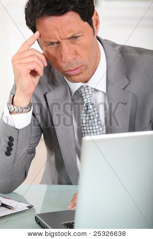 Businessman with a puzzled expression looking at a computer screen