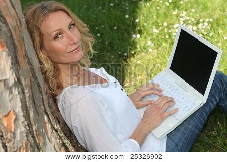 Woman under a tree using a laptop with a screen left blank for your message