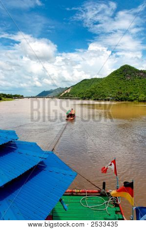 Party Boat Towing Raft Down River In Asia