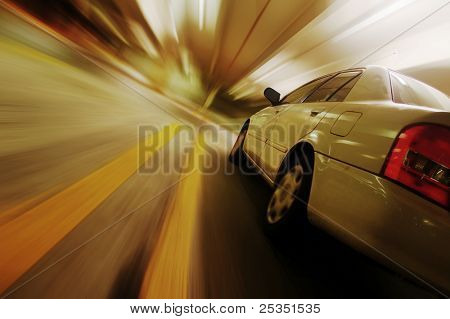 Car driving fast down interior tunnel.