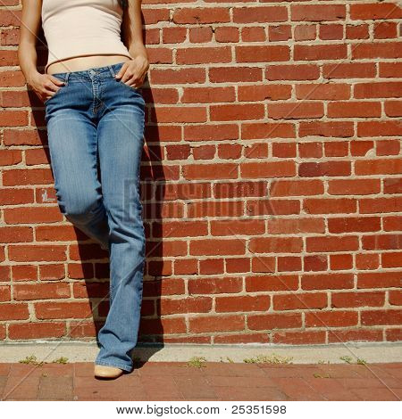 Fashionable closeups of Chinese woman's mid section against brick wall.