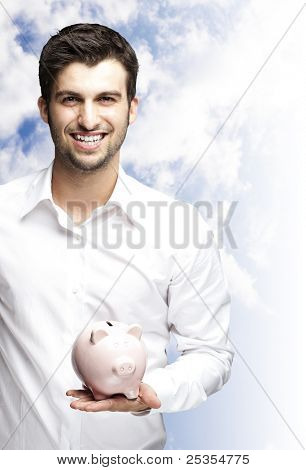 portrait of young man smiling and holding a piggy bank against a cloudy sky background