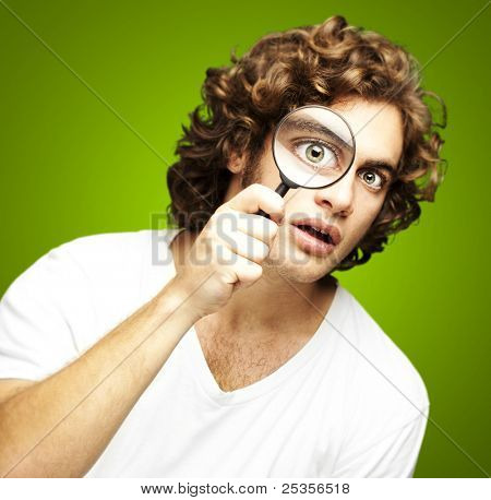 portrait of young man looking through a magnifying glass against a green background