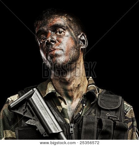 portrait of young soldier painted with jungle camouflage holding riffle over black background