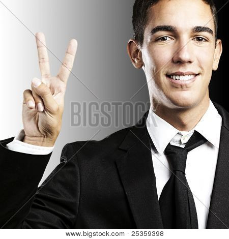 portrait of business man doing victory symbol against a white background