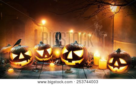 poster of Scary horror background with halloween pumpkins jack o lantern, placed on wooden deck. Old town stre