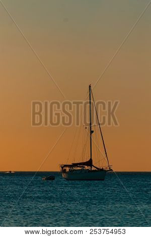poster of Silhouettes At The Beach During A Beautiful Sunset On A Cloudy Evening Boats And Sea, Sunset Time, S