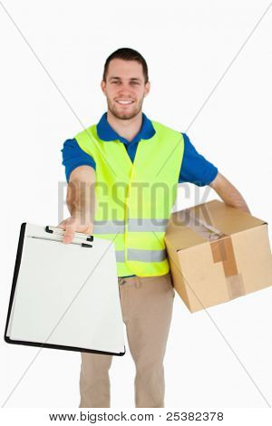 Smiling young delivery man handing over delivery bill for signature against a white background
