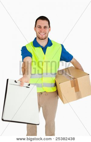 Smiling young delivery man handing over delivery note for signature against a white background