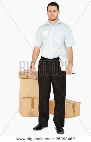 Young post employee with parcels and clipboard against a white background
