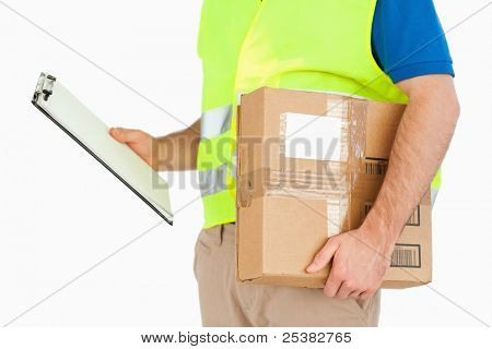Side view of delivery man with delivery note and parcel against a white background